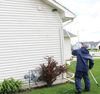 Pressure washing a residential home's exterior siding